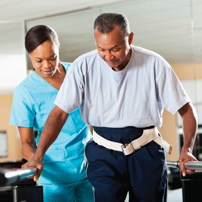 Senior man walking with help during a PT session