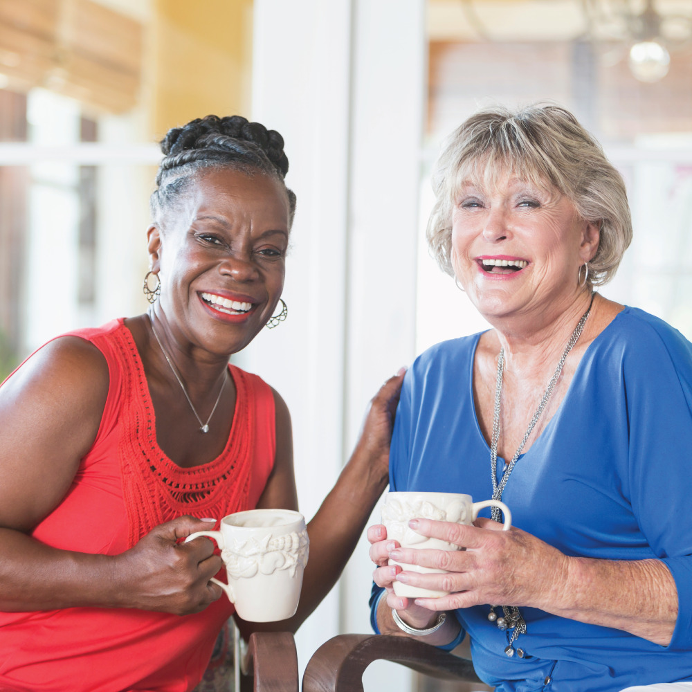 Black senior woman and white senior woman having coffee in a resident's home
