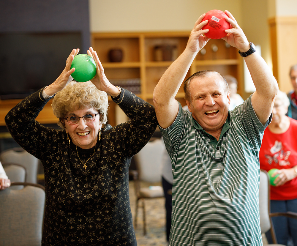 Senior woman and man participating in ball yoga